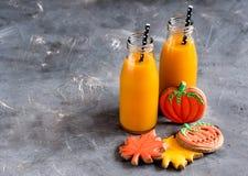 Dos botellas de jugo de la calabaza con la comida y los dulces horizontales de Halloween de la foto de la paja negra Fotos de archivo