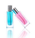 Dos botellas de perfume con reflexiones aisladas en blanco Foto de archivo
