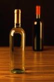 Dos botellas de vino en la tabla de madera y el fondo negro Imagen de archivo