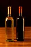 Dos botellas de vino en la tabla de madera y el fondo negro Fotos de archivo