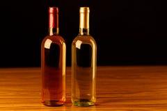 Dos botellas de vino en la tabla de madera y el fondo negro Imágenes de archivo libres de regalías