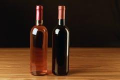 Dos botellas de vino en la tabla de madera y el fondo negro Foto de archivo libre de regalías