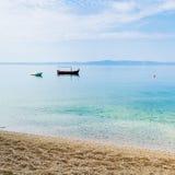 Dos botes pequeños en agua tranquila cerca de la orilla arenosa Fotografía de archivo