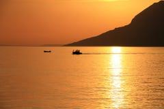Dos botes pequeños en la puesta del sol hermosa Fotos de archivo