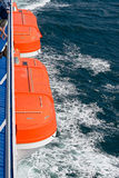 Dos botes salvavidases anaranjados en un transbordador en el mar Foto de archivo