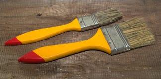 Dos brochas 1 pulgada de ancho y 2 pulgadas de ancho con las manijas amarillas en un fondo de madera foto de archivo libre de regalías