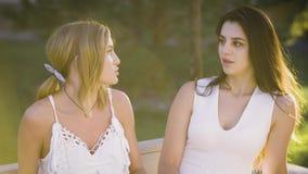 Dos buenos amigos están teniendo una conversación sincera hacia fuera sobre un banco de parque Las muchachas que llevan los vesti almacen de metraje de vídeo