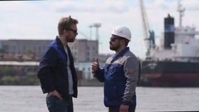 Dos buenos amigos, estibadores, compañeros de trabajo y colleages dan el alto cinco en puerto del buque mercante almacen de video
