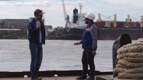 Dos buenos amigos, estibadores y colleages dan el alto cinco y dicen adiós en puerto del buque mercante almacen de metraje de vídeo