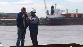 Dos buenos amigos, estibadores y colleages miran smartphone en puerto del buque mercante metrajes