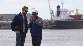 Dos buenos amigos, estibadores y colleages miran smartphone y dicen adiós en puerto del buque mercante almacen de metraje de vídeo