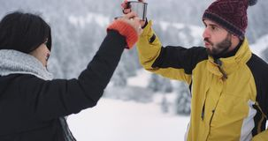 Dos buenos amigos mujer y hombre beben té caliente para conseguir calientes en el medio de bosque nevoso, ellos bebida feliz almacen de video
