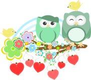 Dos buhos y pájaros lindos en la ramificación de árbol de la flor Imágenes de archivo libres de regalías