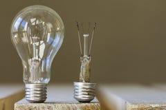 Dos bulbos de la luz eléctrica, uno bueno y otro quebrado Extracto foto de archivo libre de regalías