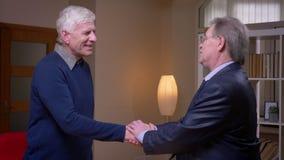 Dos businesspartners mayores sacuden las manos alegre que hacen un contrato en el fondo de los estantes almacen de video