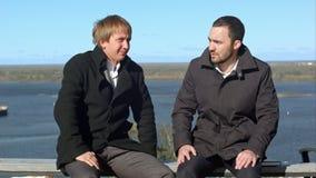 Dos businesspersons que se sientan y que hablan almacen de video