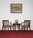 Dos butacas de madera, pequeña mesa de centro redonda y aparato de teléfono Imágenes de archivo libres de regalías