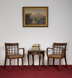 Dos butacas de madera, pequeña mesa de centro redonda y pintura enmarcada Imagen de archivo libre de regalías