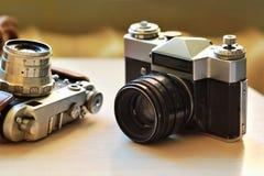 Dos cámaras de la foto del vintage de la escuela vieja en la tabla marrón clara Uno en tenedor de cuero retro marrón del caso Foto de archivo