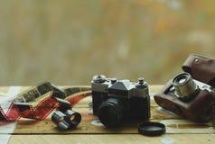 Dos cámaras de la foto del vintage de la escuela vieja y películas dispersadas en la tabla marrón clara Uno en tenedor de cuero r Fotos de archivo libres de regalías