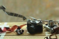 Dos cámaras de la foto del vintage de la escuela vieja y películas dispersadas en la tabla marrón clara Uno en tenedor de cuero r Imagen de archivo