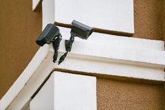 Dos cámaras del negro del CCTV en esquina del edificio imagen de archivo
