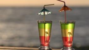 Dos cócteles con la paja en una tabla de la playa contra la perspectiva del mar en el sol, primer almacen de metraje de vídeo