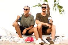 Dos cócteles de la bebida de los individuos en una playa tropical imagen de archivo