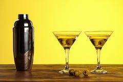 Dos cócteles en los vidrios de martini con las aceitunas verdes y la coctelera en una superficie de madera contra fondo amarillo  imagen de archivo