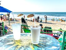 Dos cócteles en una tabla del sol con vista de la playa mexicana en Sayulita imagen de archivo libre de regalías