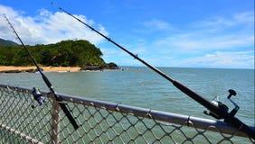 Dos cañas de pescar en el embarcadero Queensland Australia de la ensenada de la palma Foto de archivo