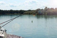 Dos cañas de pescar en el fondo de un río y de un bosque imágenes de archivo libres de regalías