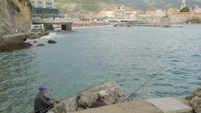 Dos cañas de pescar de los pescadores que hacen girar por el mar en Budva almacen de video