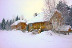 Dos cabañas de madera en el fondo del bosque del invierno Imágenes de archivo libres de regalías