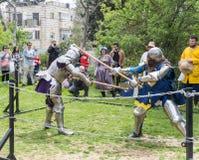 Dos caballeros con las alabardas luchan en el anillo en el festival de Purim con rey Arthur en la ciudad de Jerusalén, Israel fotografía de archivo
