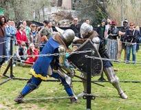 Dos caballeros con los escudos y las espadas luchan en el anillo en el festival de Purim con rey Arthur en la ciudad de Jerusalén imagenes de archivo