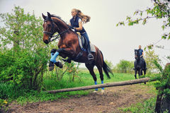 Dos caballos de montar a caballo de las muchachas en campo Fotos de archivo libres de regalías