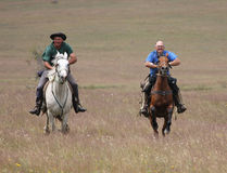 Dos caballos de montar a caballo de los hombres a la velocidad Fotografía de archivo