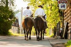 Dos caballos de montar a caballo de los hombres Gente vestida en trajes populares foto de archivo