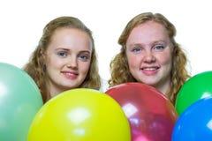 Dos cabezas de las muchachas detrás de los globos coloreados Foto de archivo