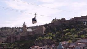 Dos cabinas que se mueven por el cablecarril Contra la perspectiva de la fortaleza de Narikala y de la iglesia de San Nicolás, en almacen de video