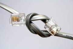 Dos cables para la transmisión de datos con las extremidades anudadas fotografía de archivo