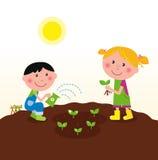Dos cabritos felices que riegan y que plantan las plantas Foto de archivo libre de regalías