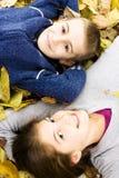 Dos cabritos lindos que se acuestan con las hojas alrededor Foto de archivo