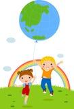 Dos cabritos que juegan con el globo de la tierra Imagen de archivo libre de regalías