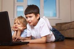 Dos cabritos que juegan el juego de ordenador Imagen de archivo libre de regalías