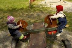 Dos cabritos que juegan en un totter del balanceo Imagen de archivo libre de regalías