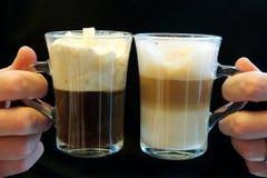 Dos cafés de lujo en las tazas de cristal, sostenidas por dos manos Imagenes de archivo