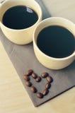 Dos cafés del café express en pequeñas tazas blancas con el corazón forman Fotos de archivo libres de regalías