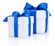 Dos cajas blancas atadas con el arco azul de la cinta de satén aislado en blanco Imágenes de archivo libres de regalías